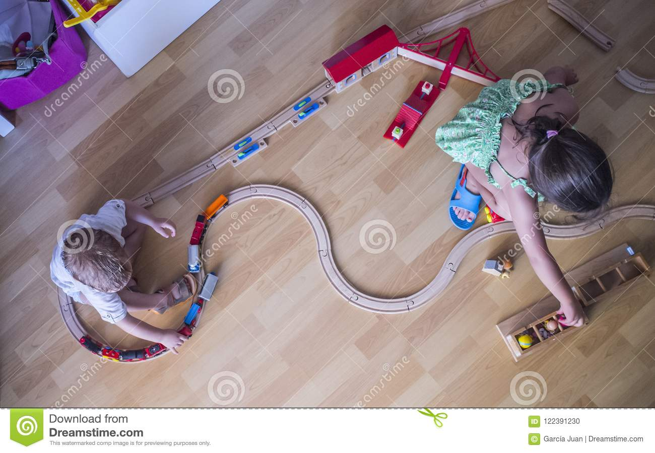 Little brothers playing with wooden toy train