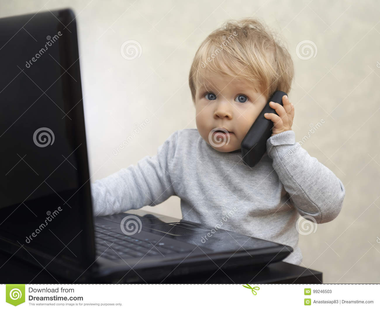 Little businessman sitting at the computer with a toy cell phone