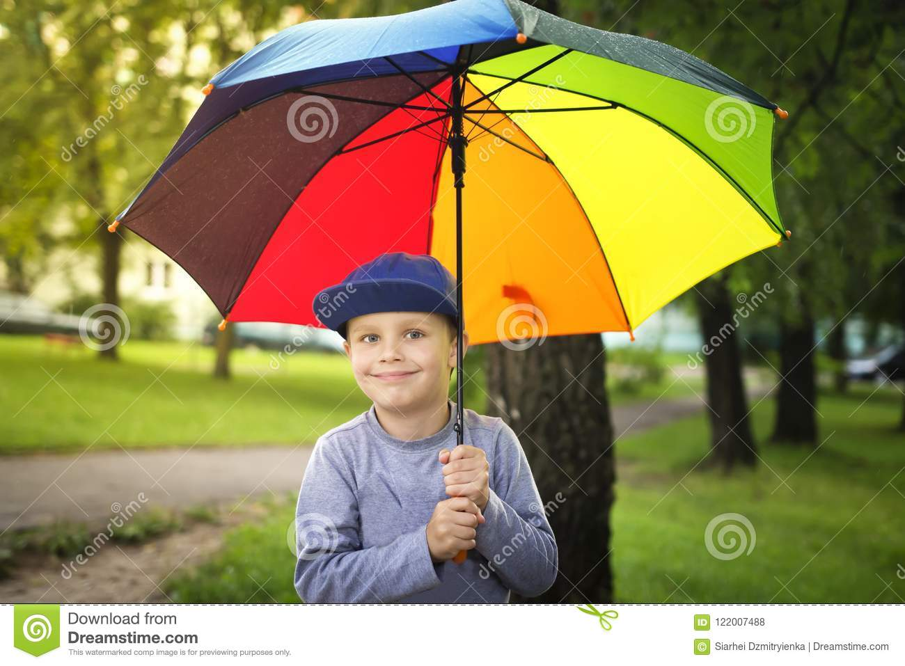 Little caucasian boy with colorful umbrella in park after rain on sunny summer day