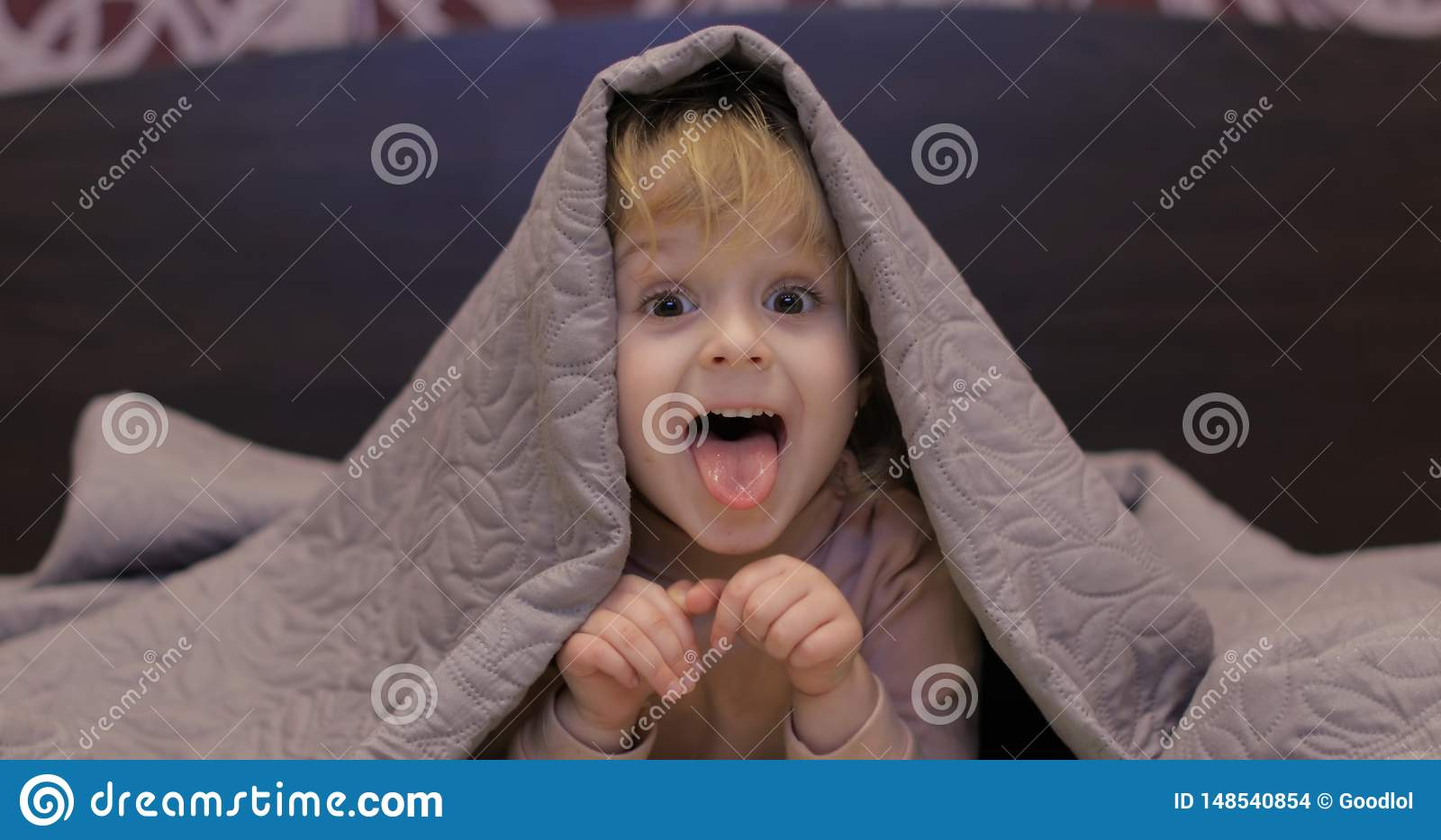 Little cheerful girl hides under blanket and watching TV. Concept of kids sleep