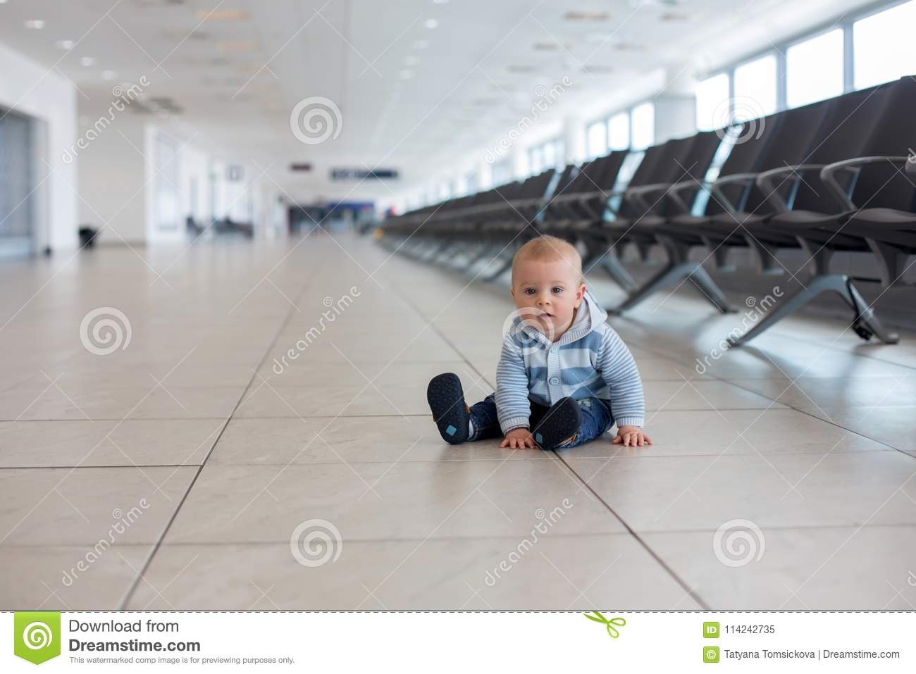 Little child, baby boy, playing at the airport, while waiting for his plane to departure