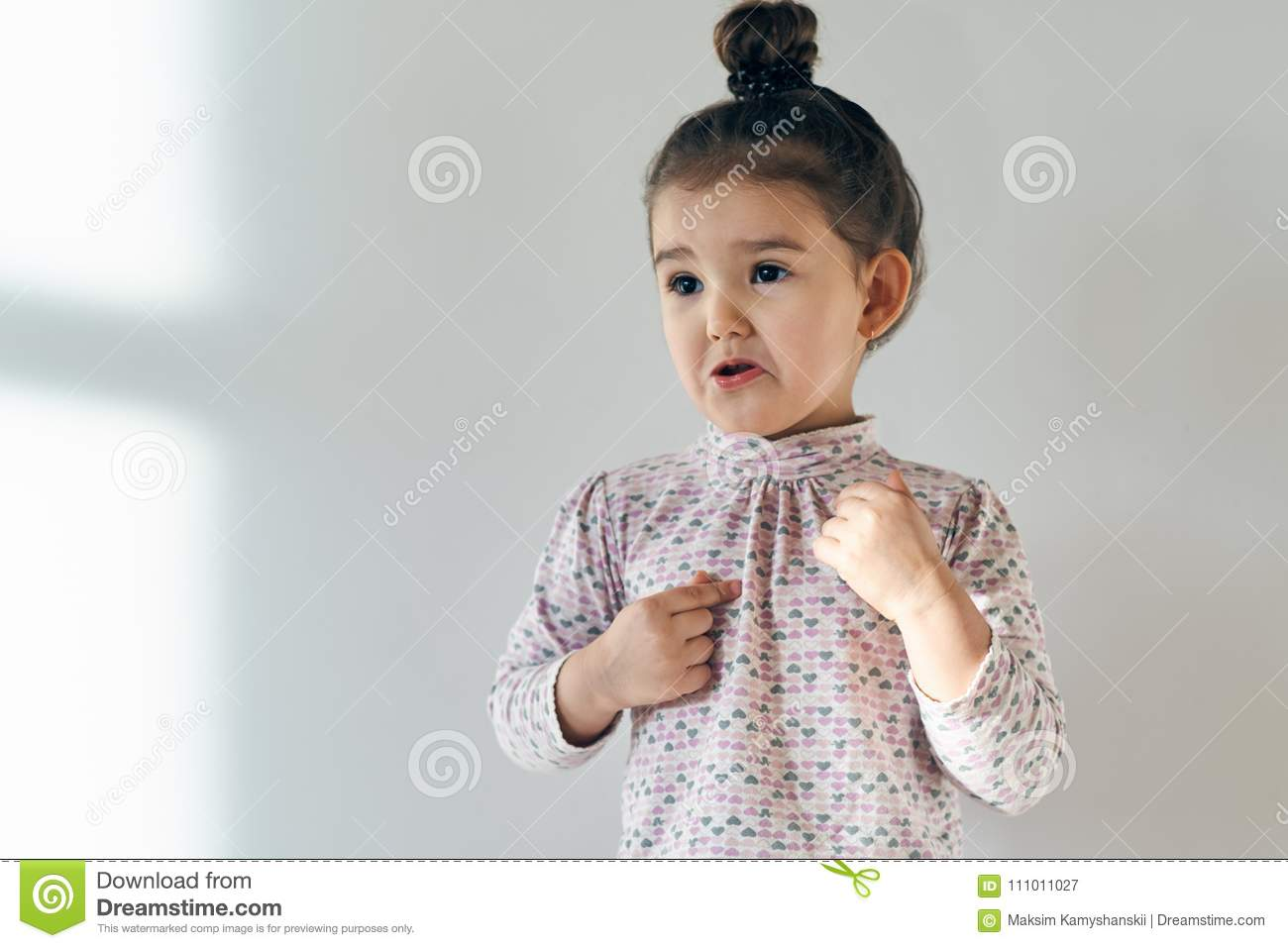 Little child baby girl with her hair gathered in a bun on top upset and outraged by the injustice.