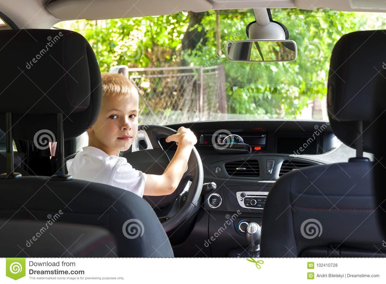 Download Little Child Boy Behind The Steering Wheel Of A Car Stock Photo