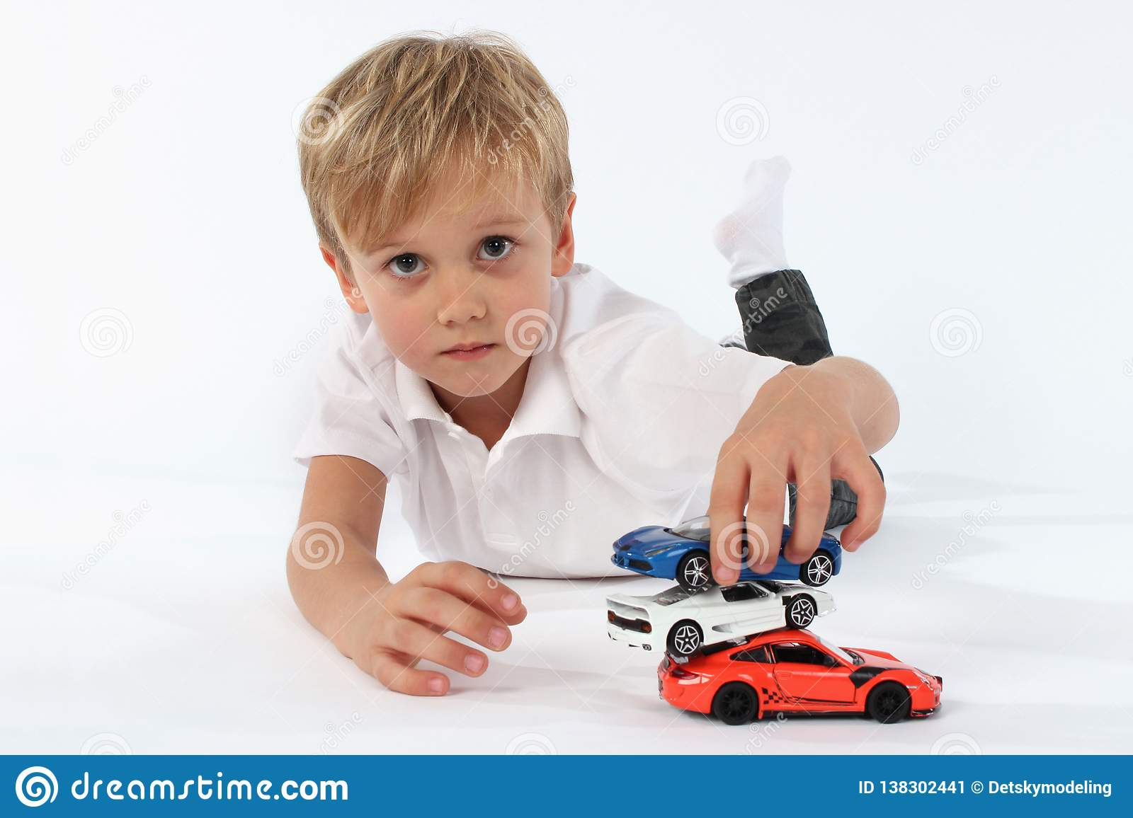 Little child boy playing satisfyingly with his toys and building a tower of the cars