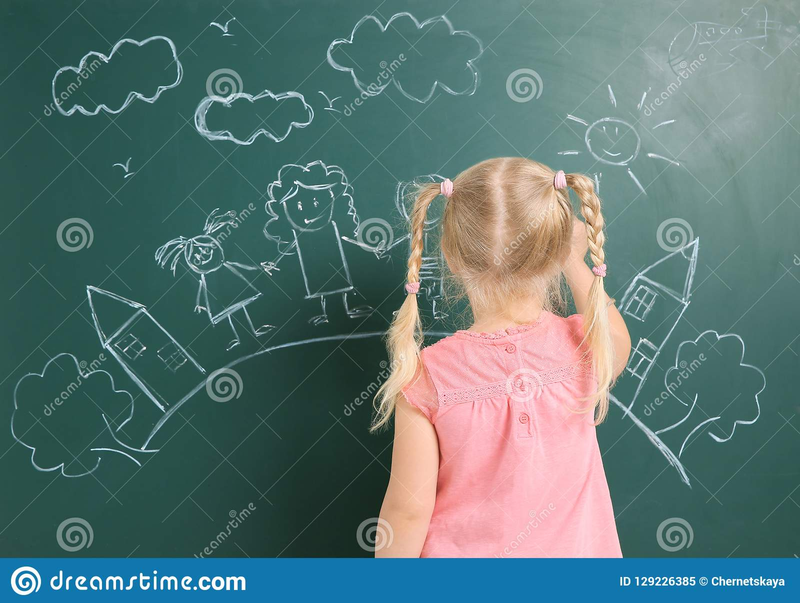 Little child drawing family with white chalk