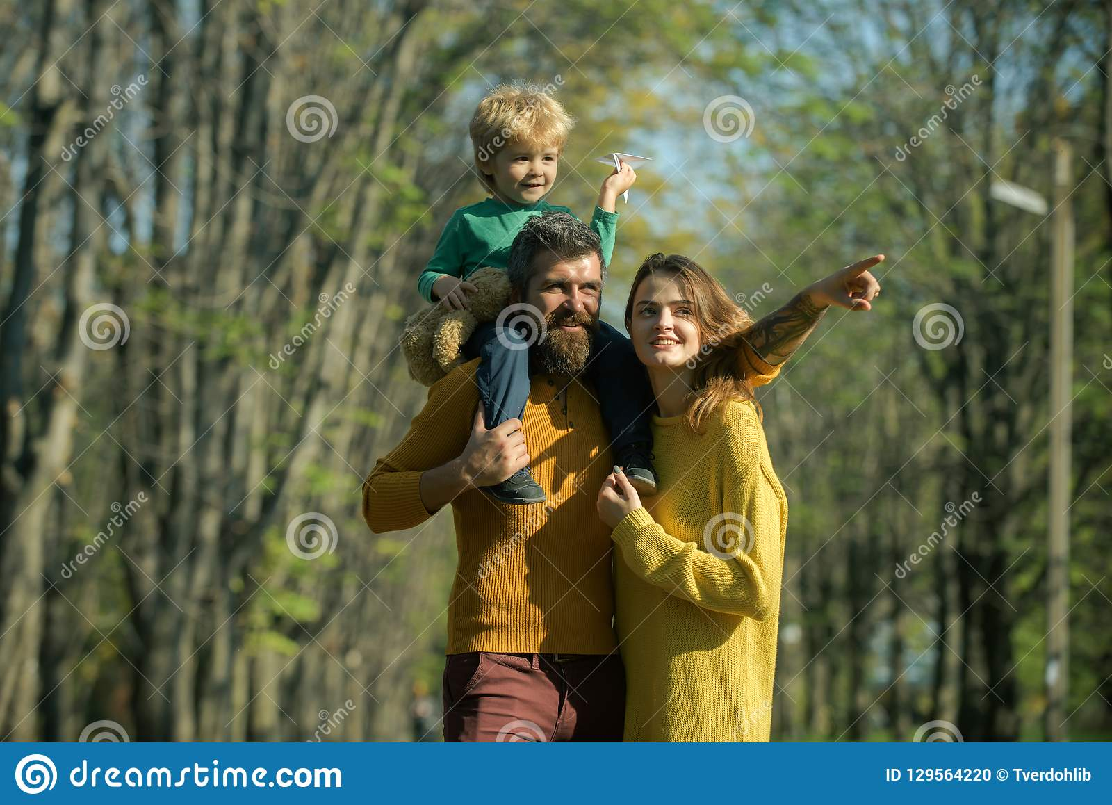 Little child dreaming about travelling by plane. Family launch paper plane in park, dreaming concept. Fly high under the