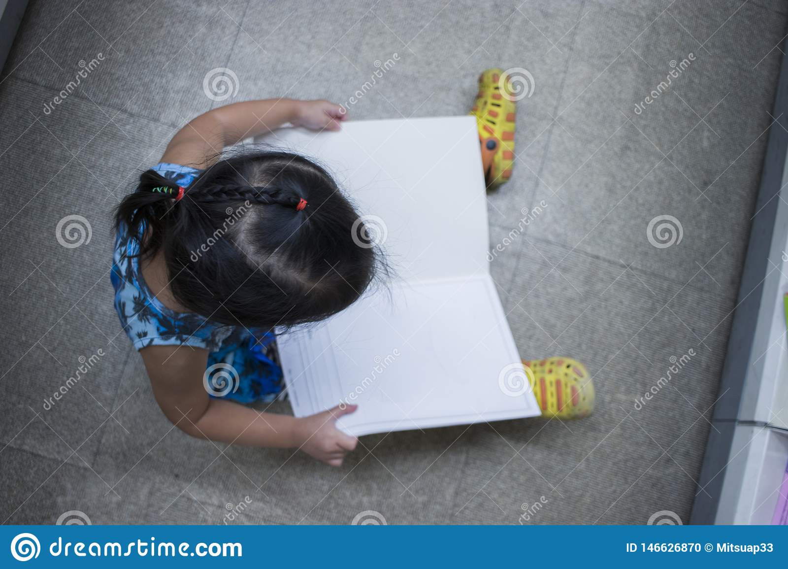 Little Child explores and reading a book in book store top view