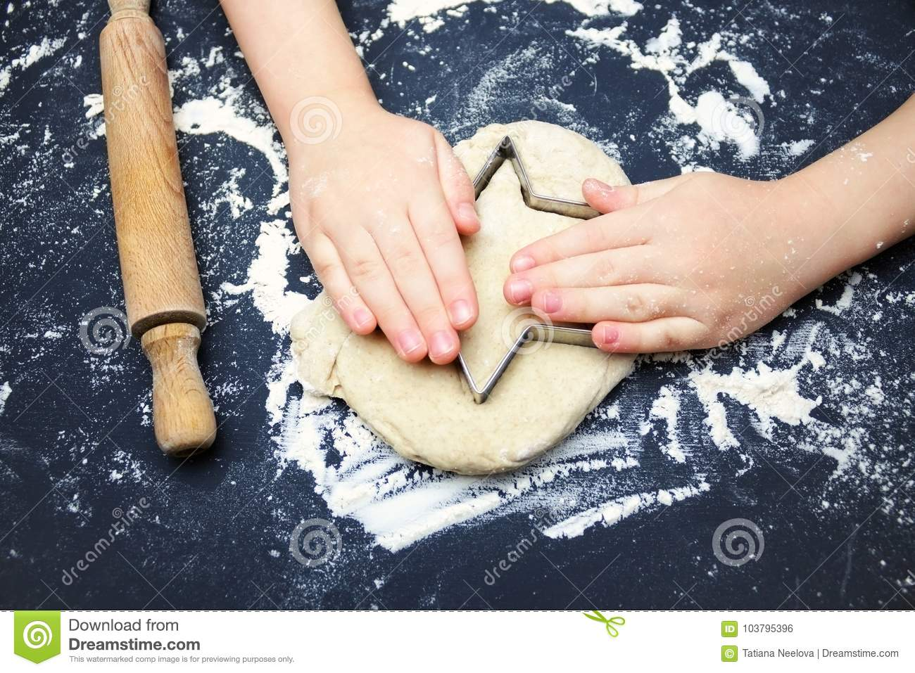 Little child hands with cookie cutter like a star making handmade traditional Christmas cookies. An overhead photo of kid`s hands,
