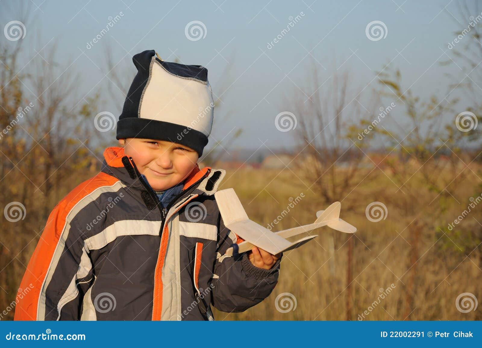 Little child holding plane model