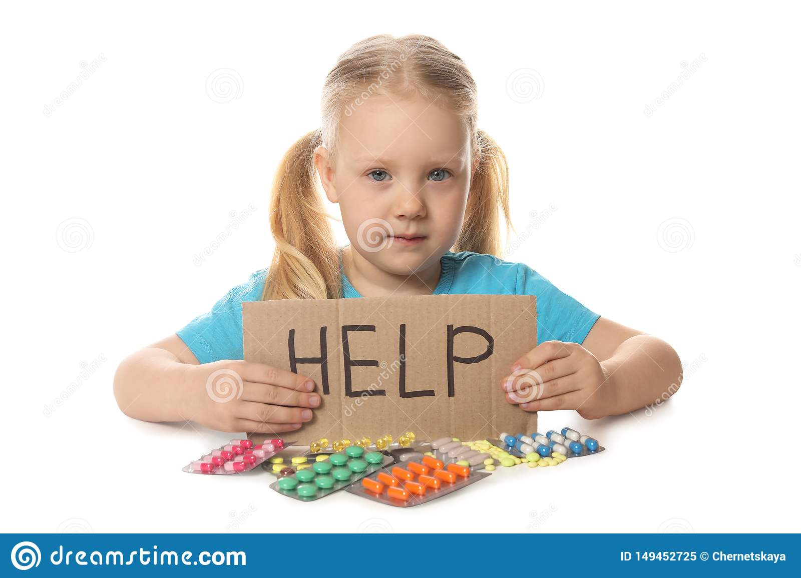 Little child with many different pills and word Help written on cardboard. Danger of medicament