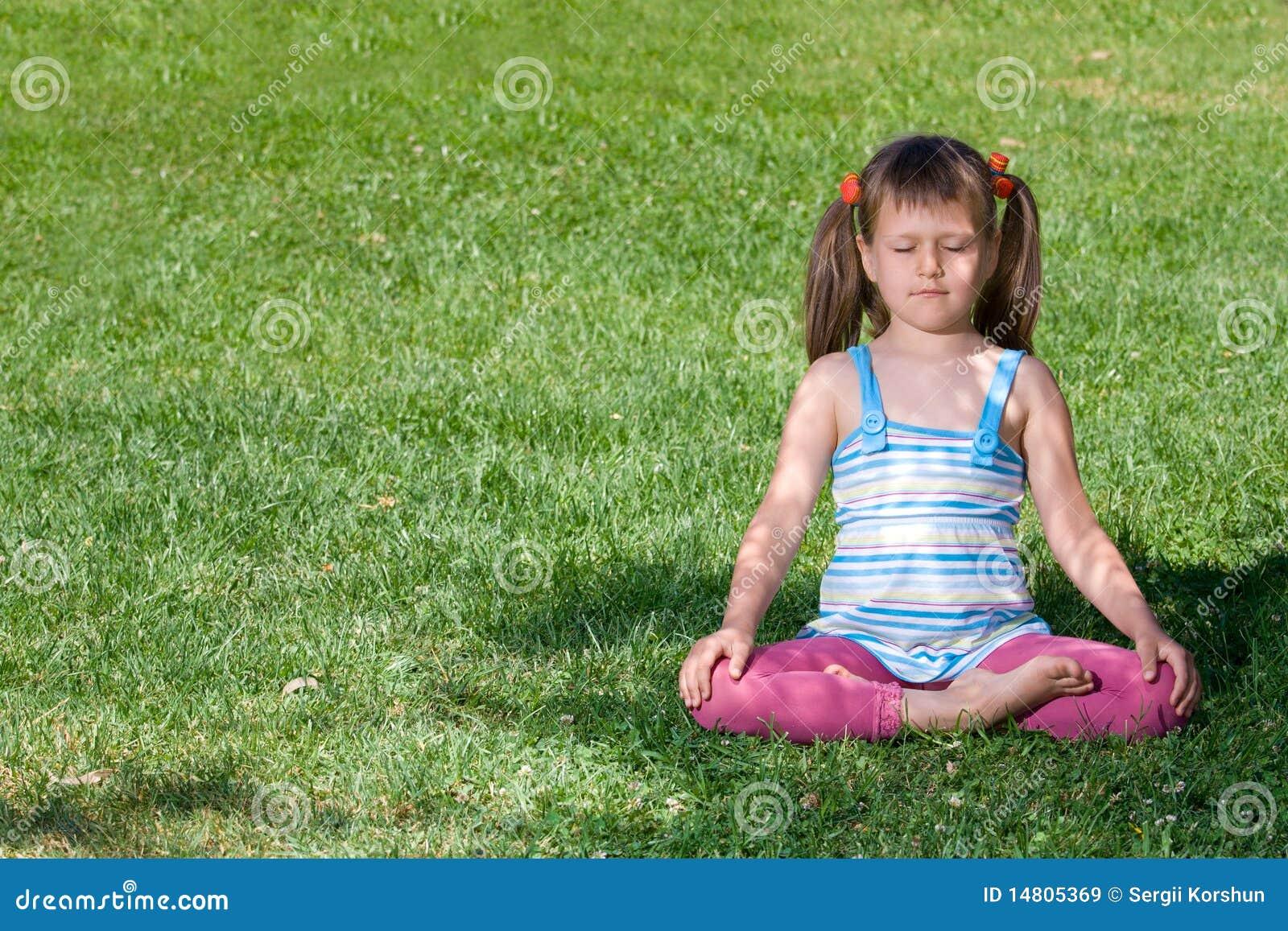Little child meditate in asana on green grass