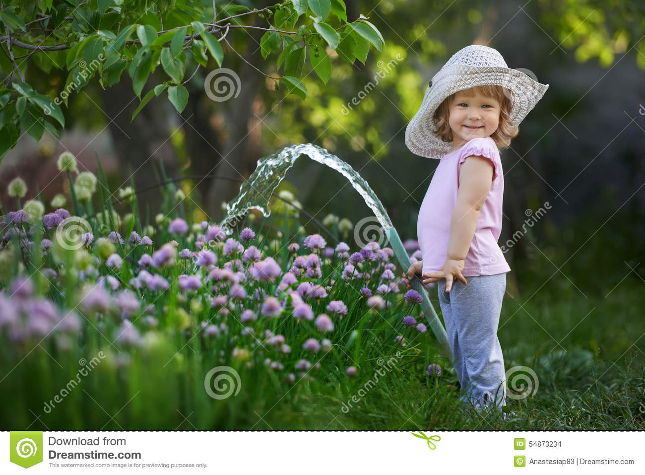 Little child watering onions in the garden