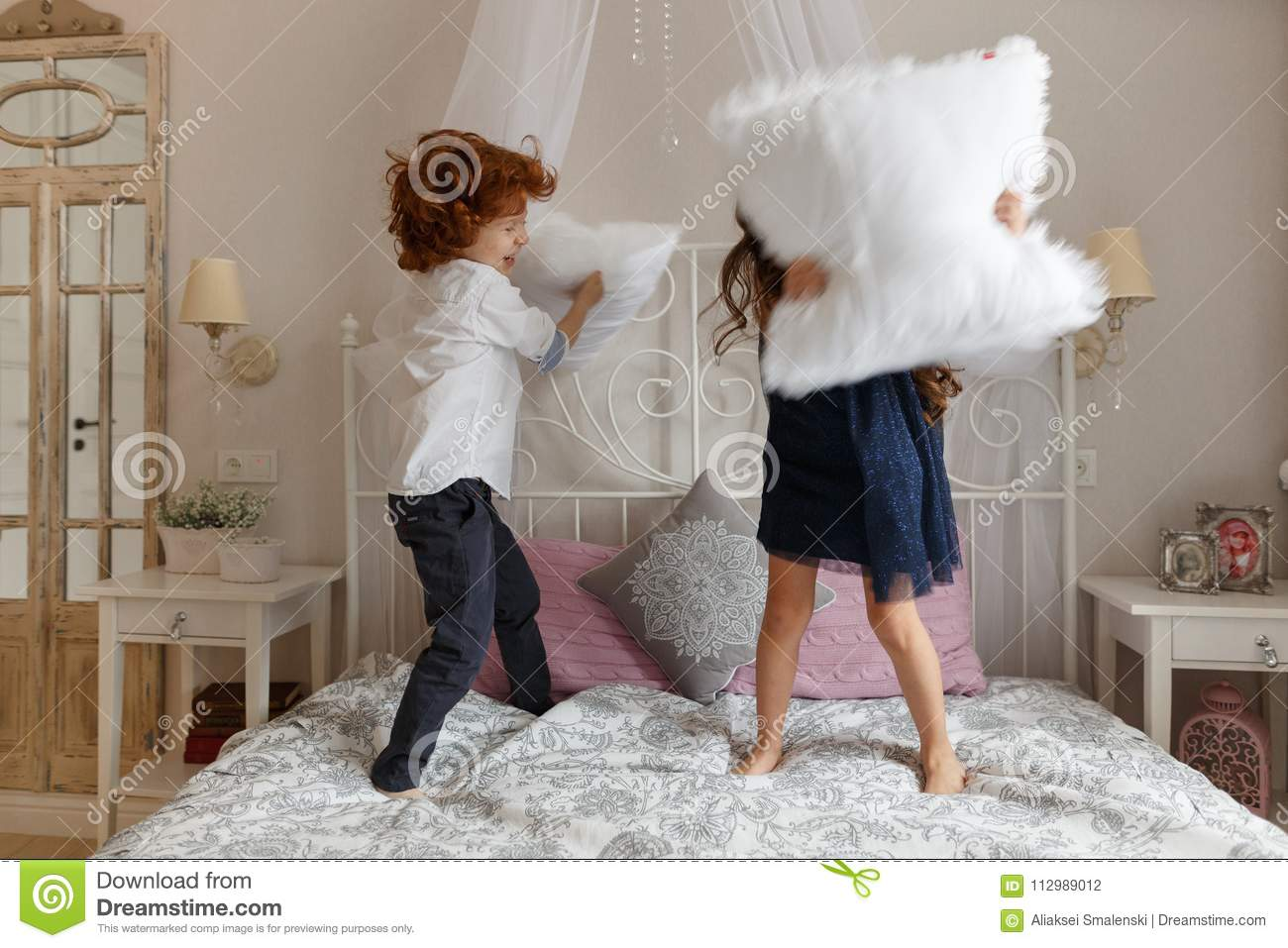 Little children, boy and girl fighting with pillows