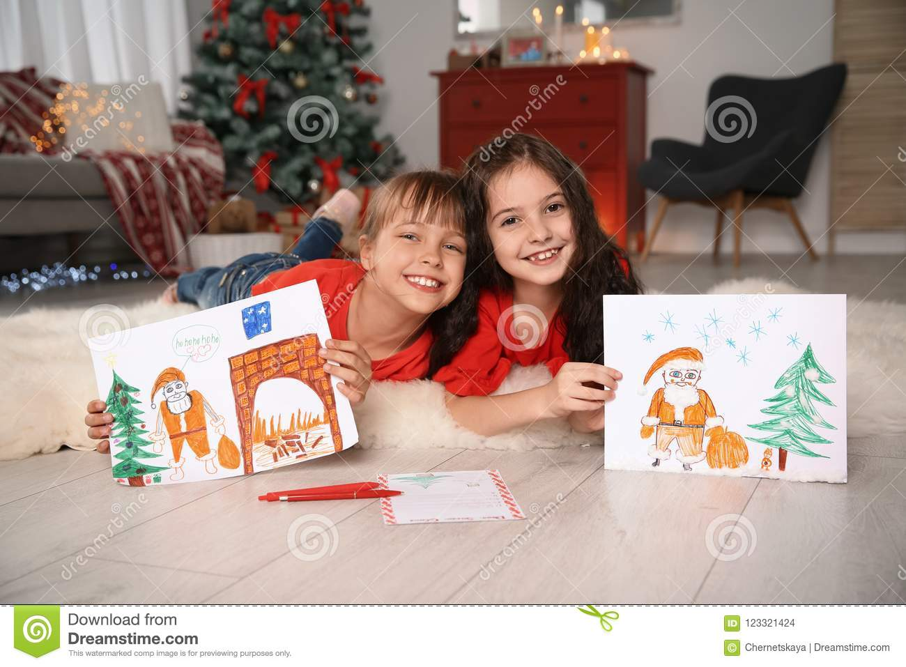Little children with drawings and letter to Santa at home
