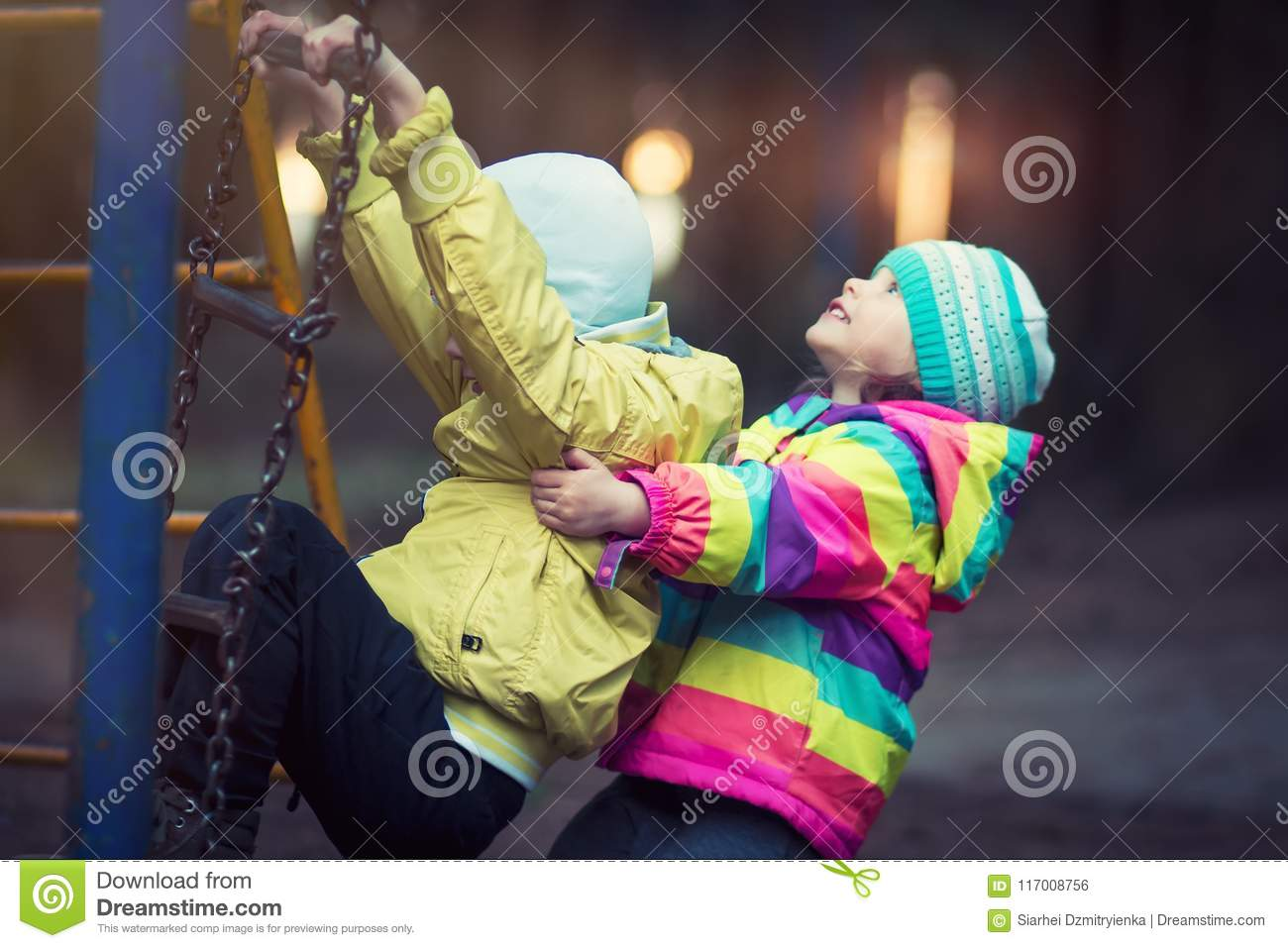 Little children play in playground in evening in park on background of shining lights.