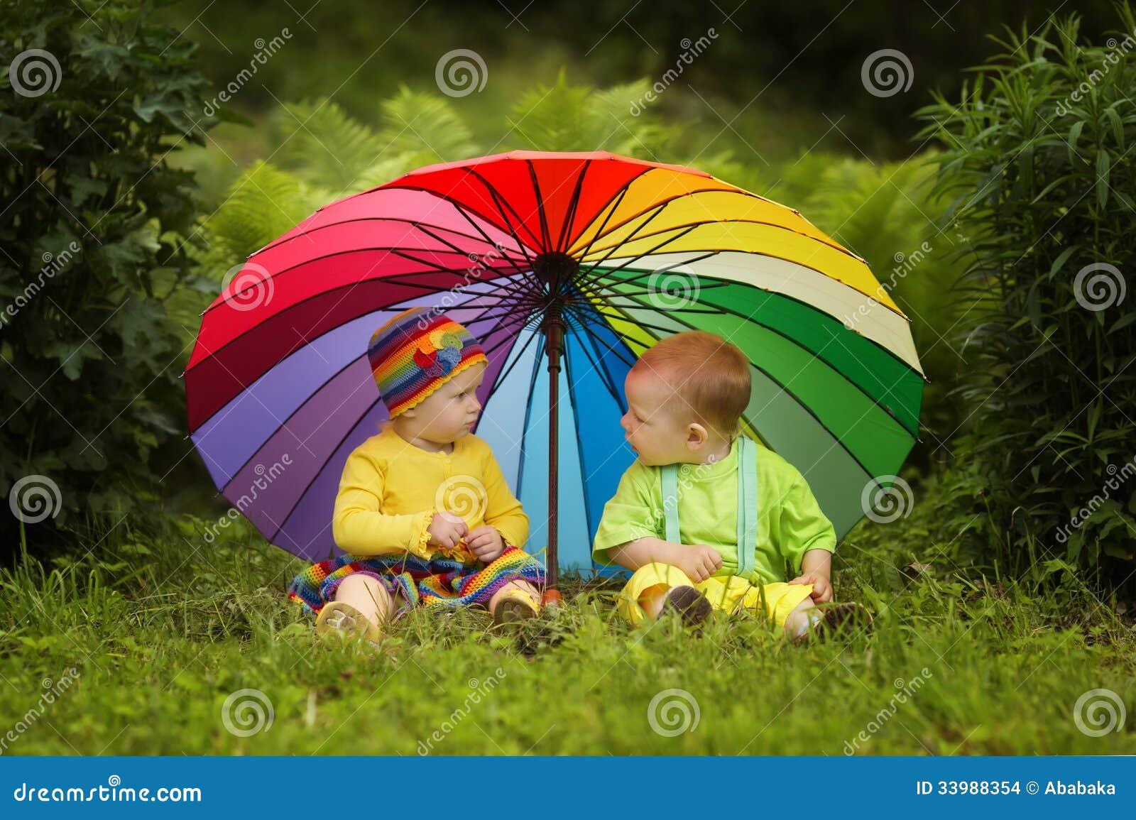 Little children under colorful umbrella