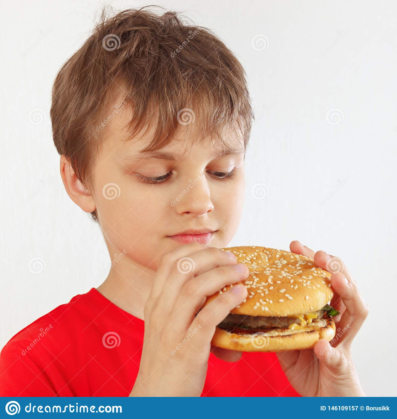 Little cut boy in a red shirt with a tasty hamburger on white background