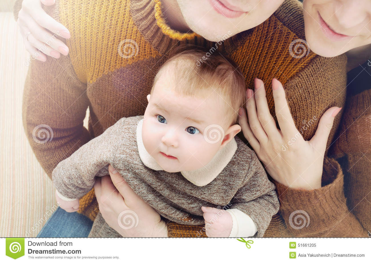 little cute baby with big eyes sitting on the parent s knees fa