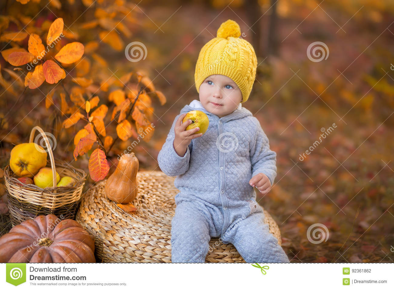 Little cute baby boy in yellow winter hat sitting on pumpkin in autumn forest alone