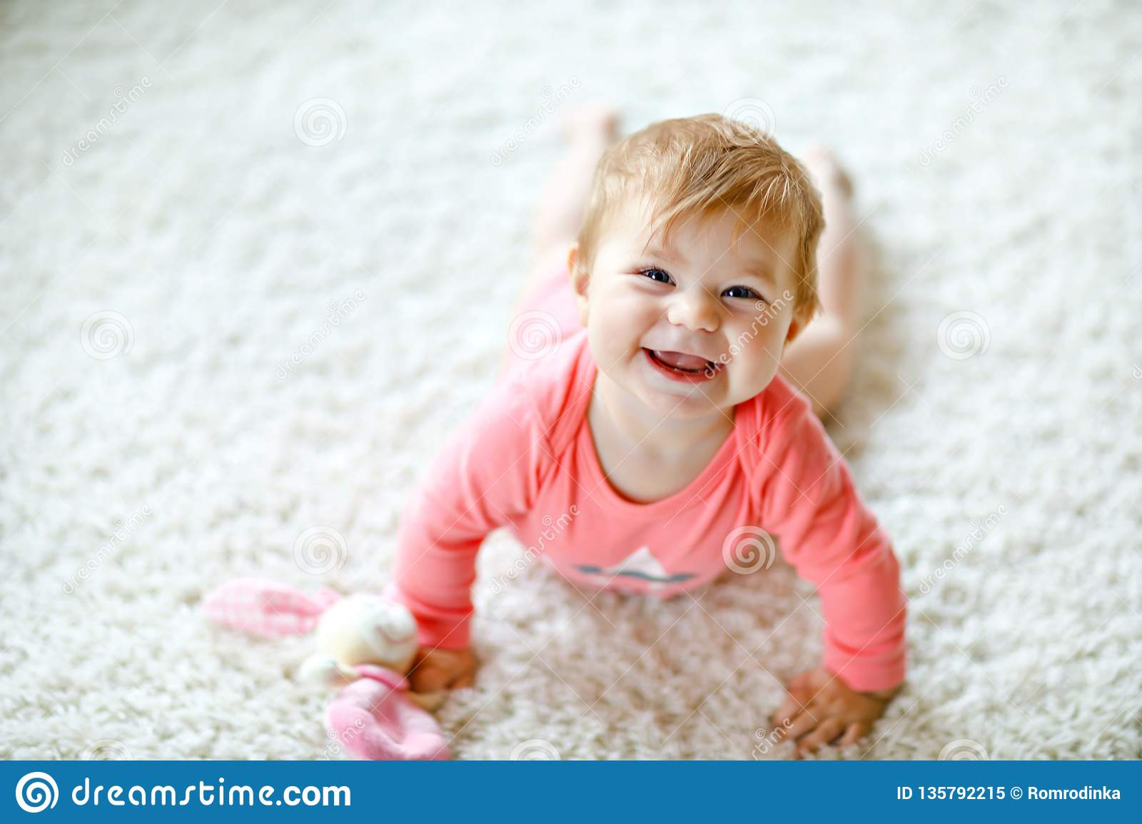 Little cute baby girl learning to crawl. Healthy child crawling in kids room with colorful toys. Back view of baby legs