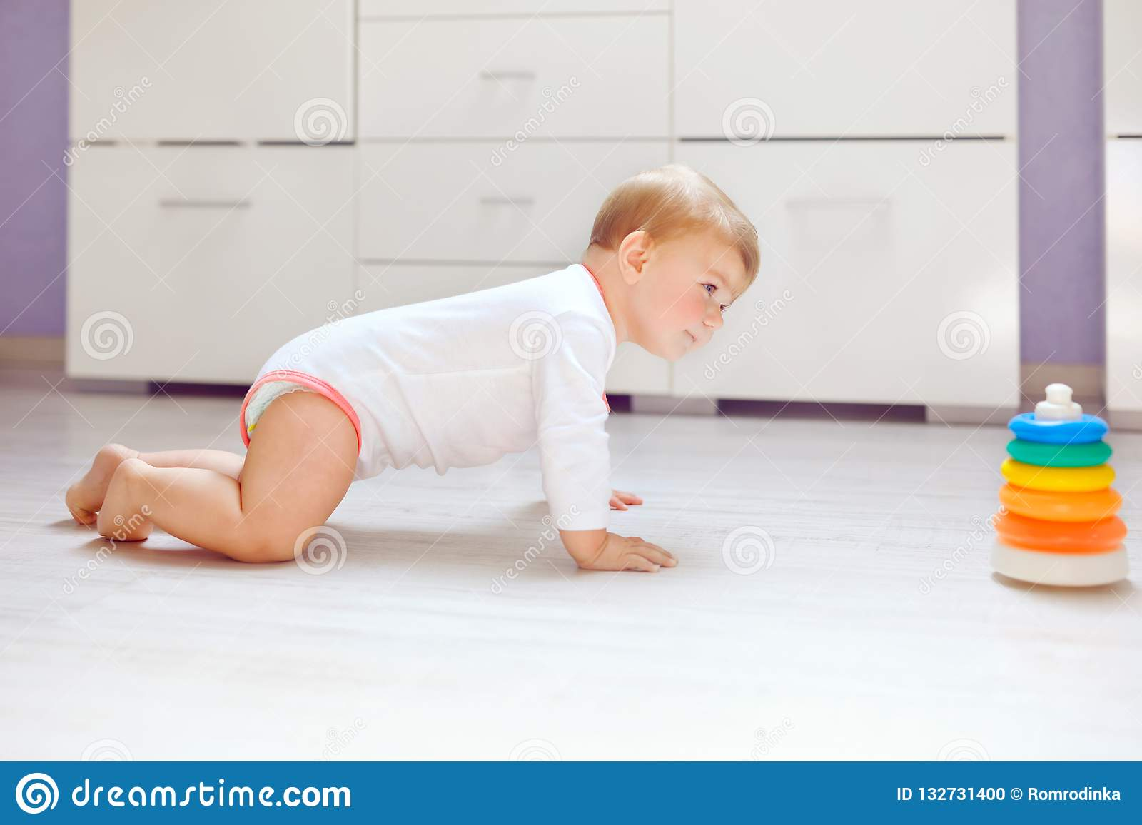 Little cute baby girl learning to crawl. Healthy child crawling in kids room. Smiling happy healthy toddler girl. Cute