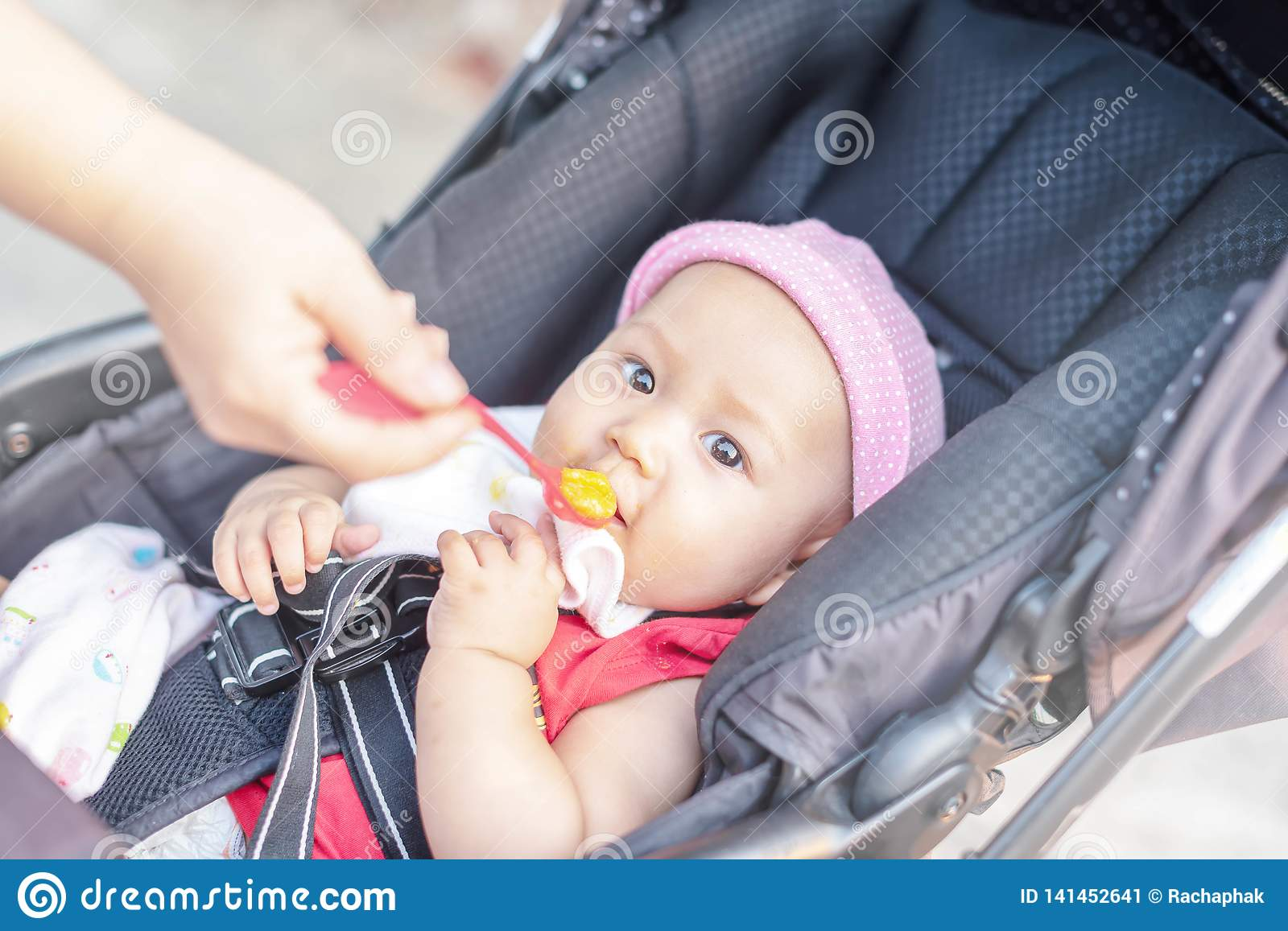 Little cute baby girl sits on a chair and eating with spoon. Mother feeding baby holding out her hand with a spoon of food made
