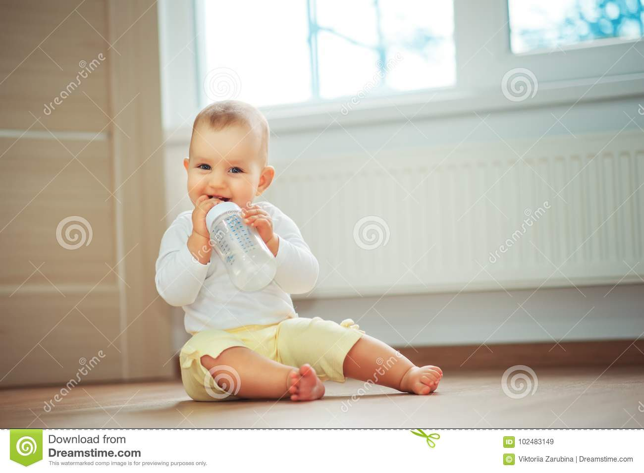 Little cute baby girl sitting in room on floor drinking water from bottle and smiling. Happy infant. Family people indoor Interior