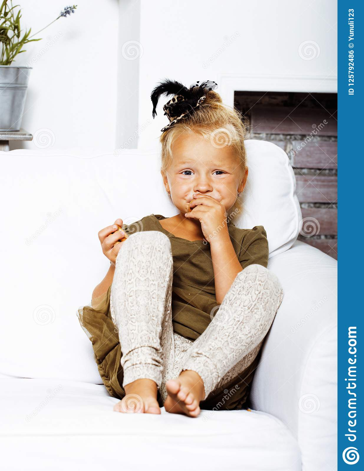 Little cute blond girl at home interior happy smiling close up,