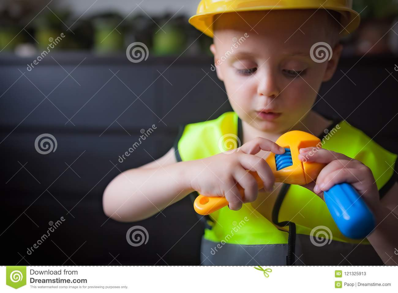 8991b9041 Little cute boy holding plastic toy tools pretending to be a builder foreman