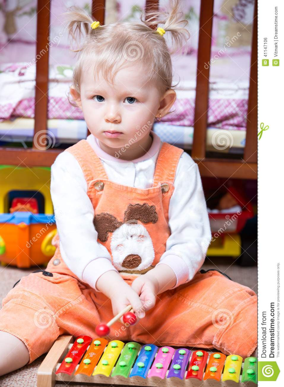 Little cute child girl with musical instrument.