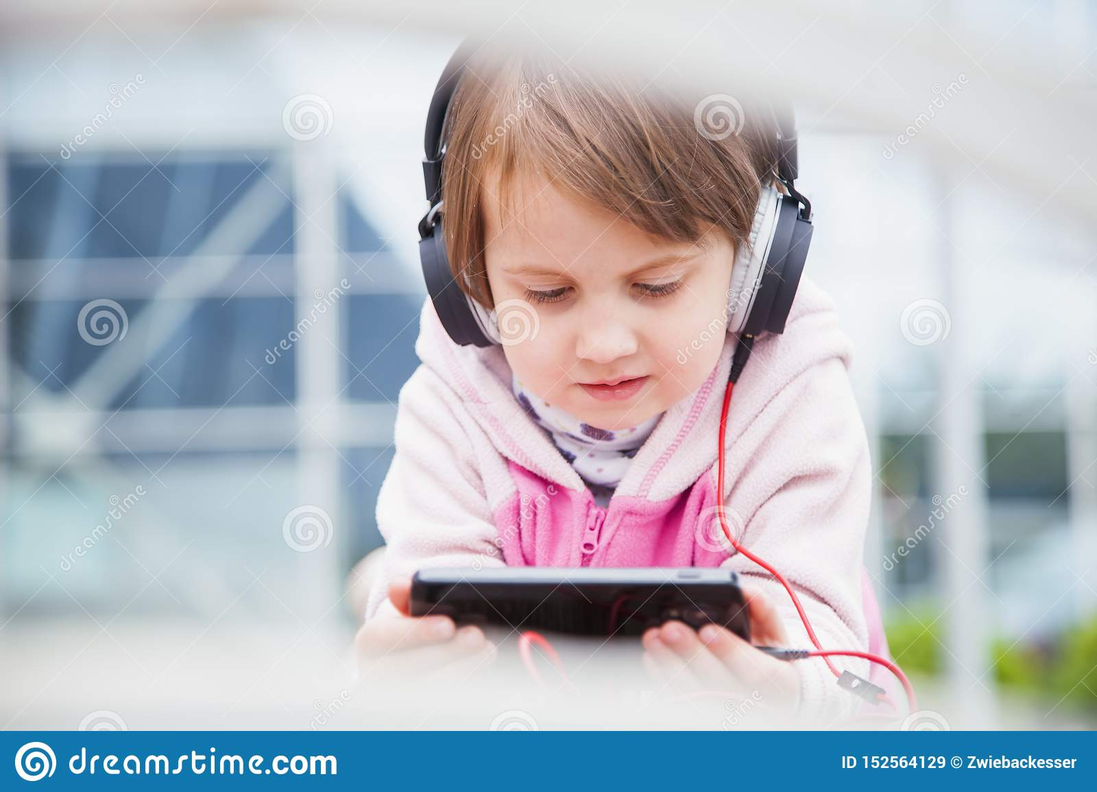 Little cute child girl wearing headphones listens online web free audio course outdoors