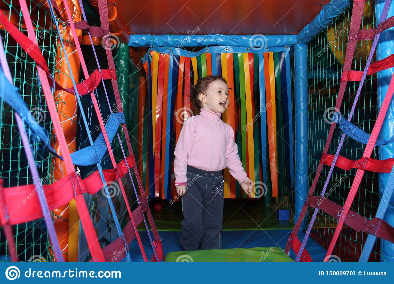 Little cute curly baby girl playing in a children`s entertainment center in the game maze. The child plays in the playground