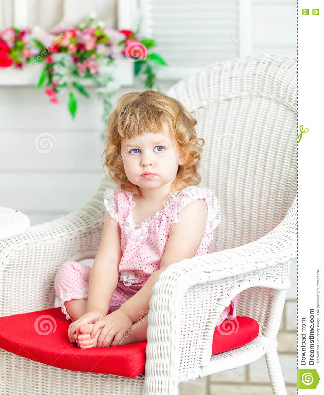 Little cute curly girl sitting on white wicker chair in the garden and looks into distance.