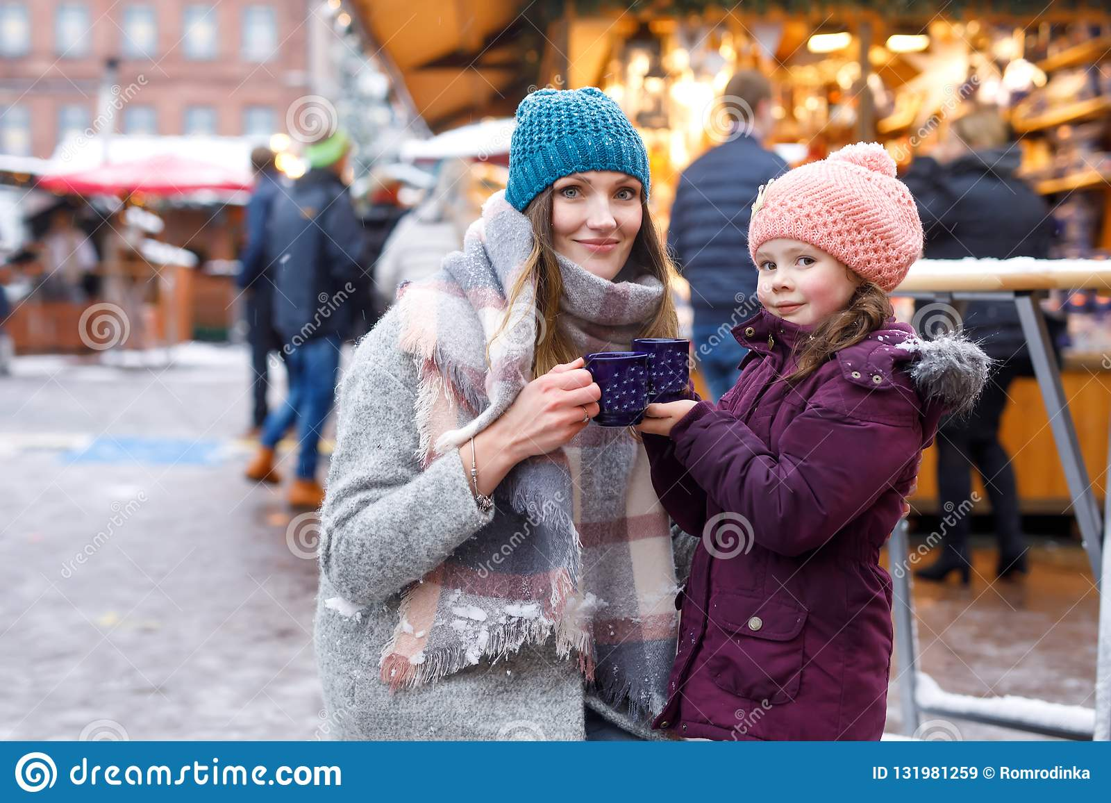 Little cute daughter and mother with cup of steaming hot chocolate or children punch. Happy child girl and beautiful