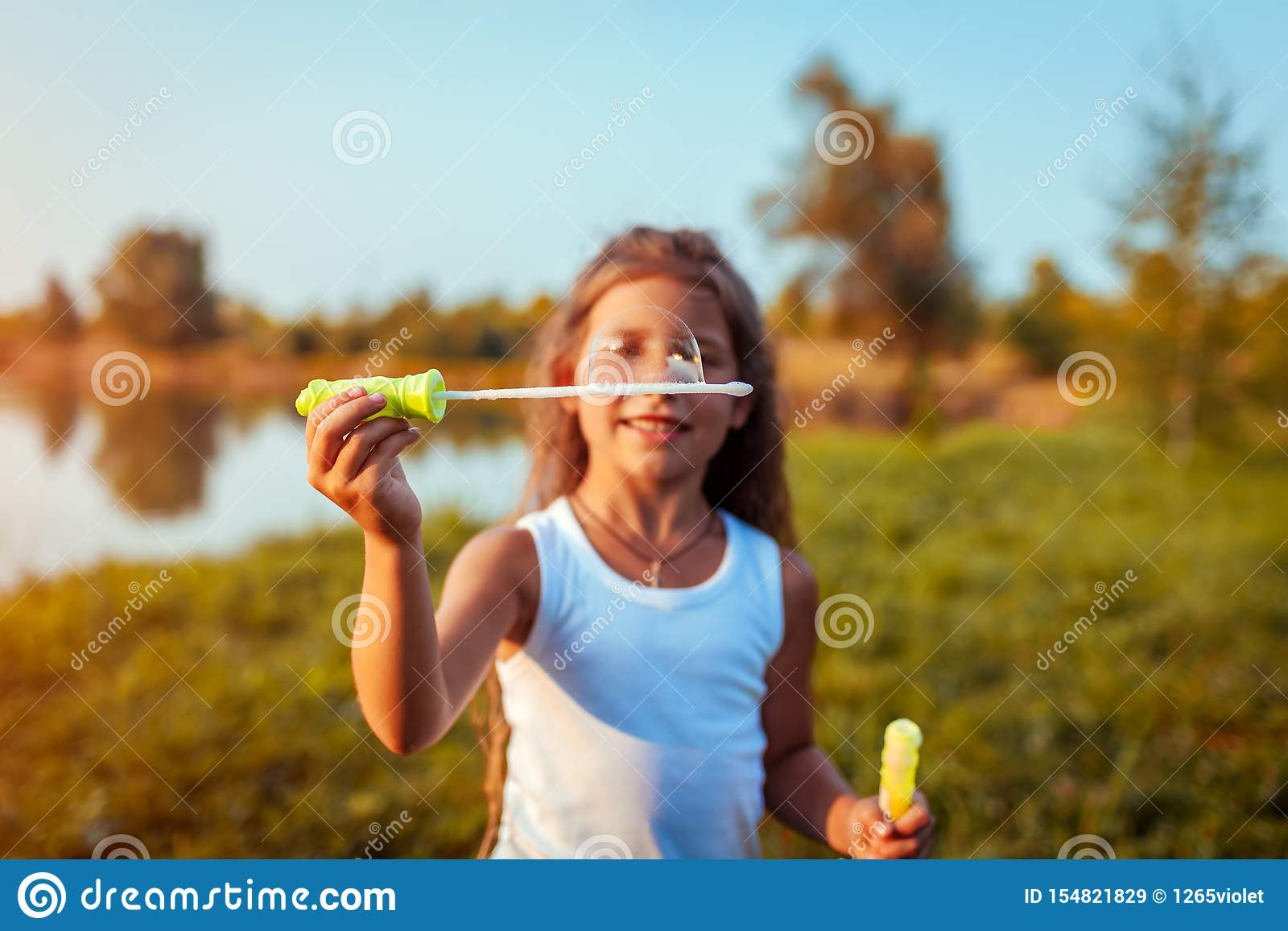 Little Cute Girl Blowing Bubbles In Summer Park By River