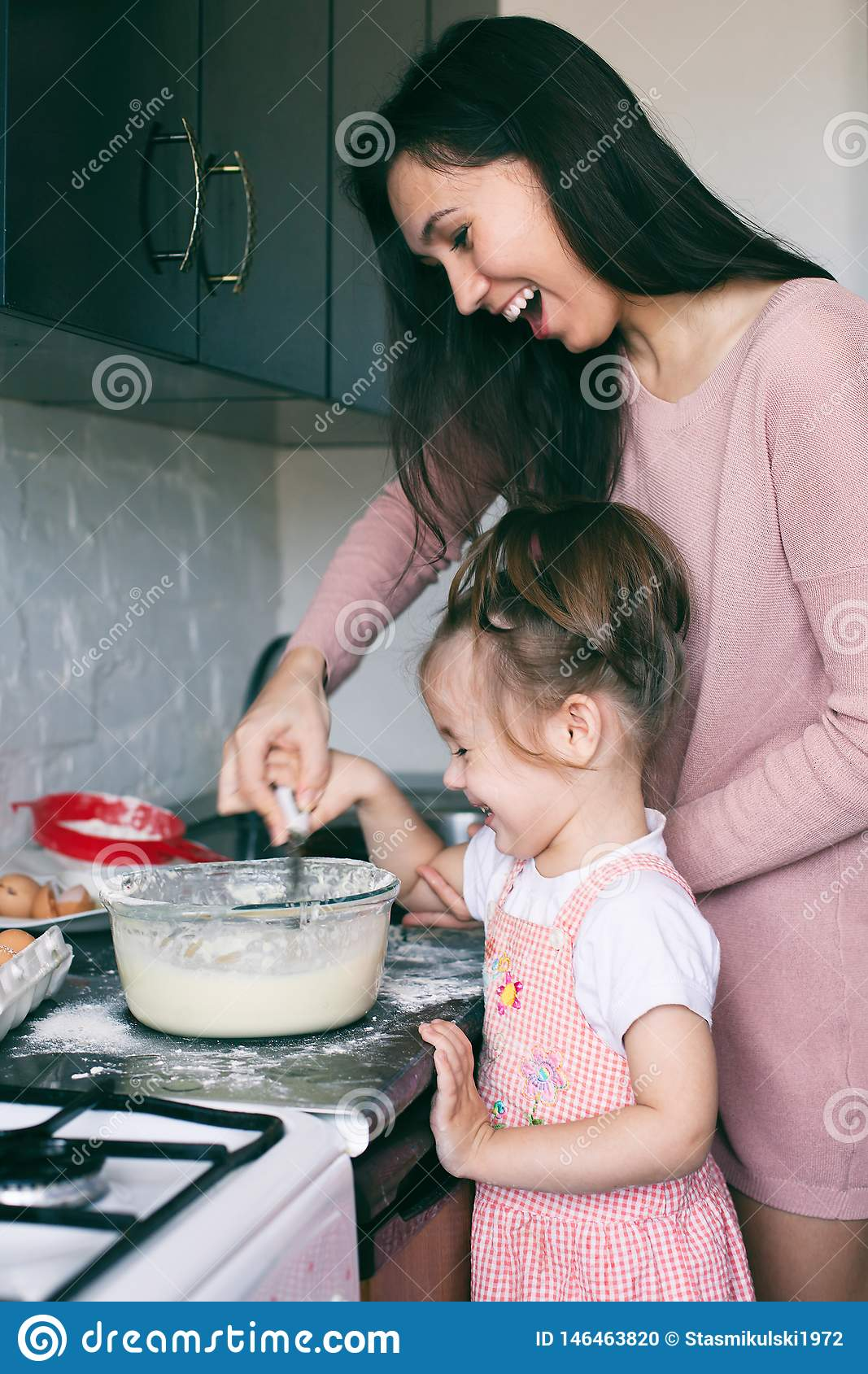 A little cute girl and her mother preparing the dough in the kitchen at home