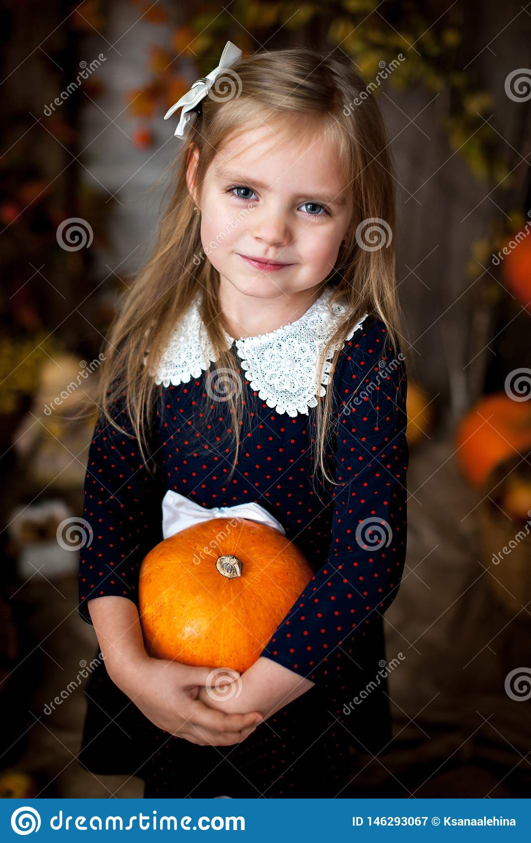 Beautiful little girl holding a pumpkin