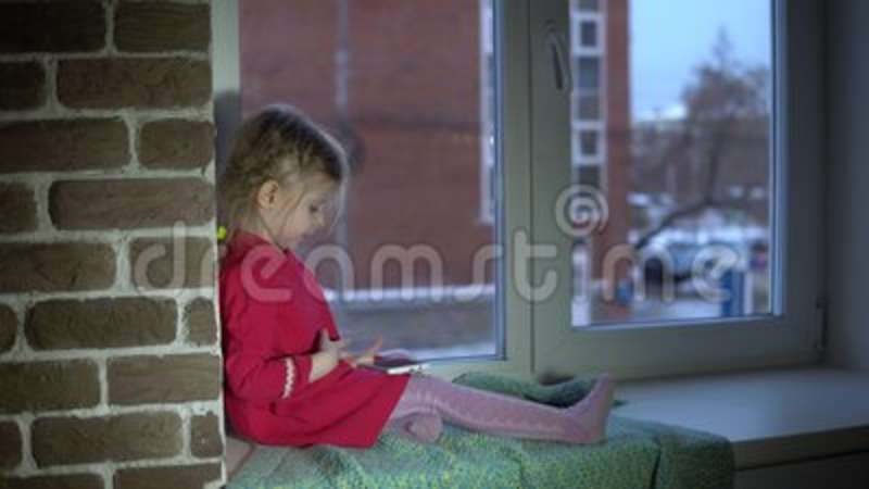 A Little Sweet Girl In A Pink Dress Sits On The Windowsill And Uses A  Smartphone Stock Footage   Video Of Happy, Portrait: 109301888