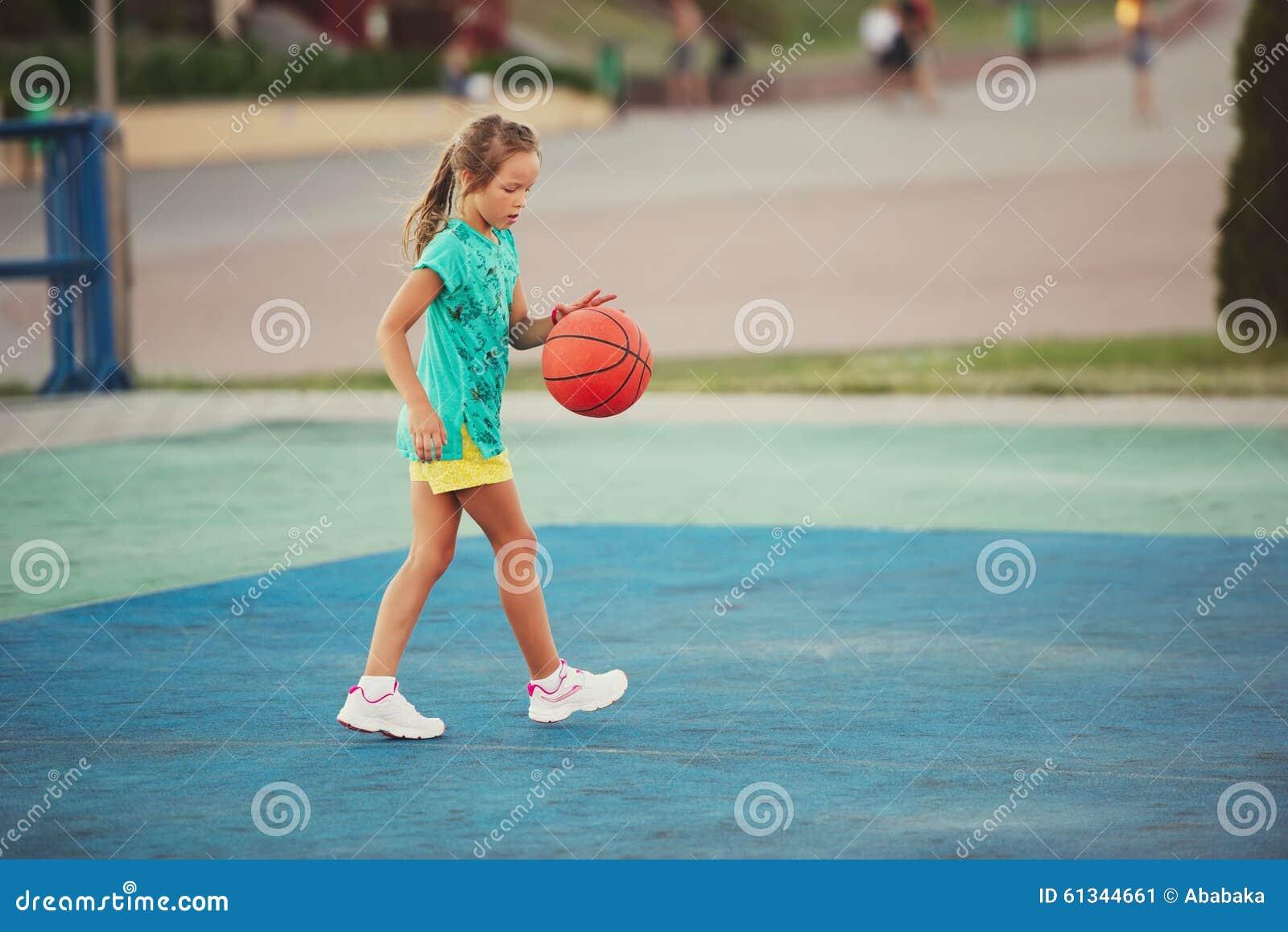A Woman Playing Basketball Imágenes De Stock A Woman: Little Cute Girl Playing Basketball Outdoors Stock Photo