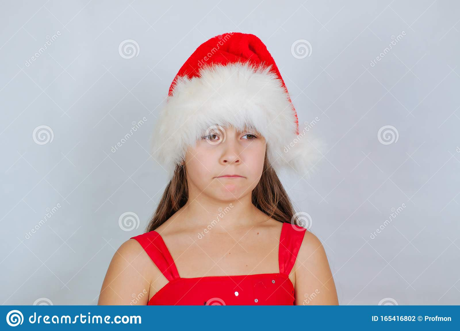 Little Cute Girl Is Standing In A Christmas Hat Is Sad Stock Photo - Image of caucasian ...