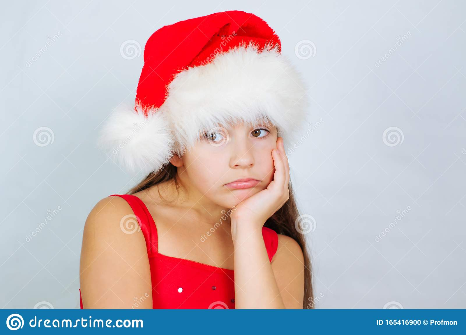 Little Cute Girl Is Standing In A Christmas Hat Is Sad Stock Photo - Image of baby, happy: 165416900