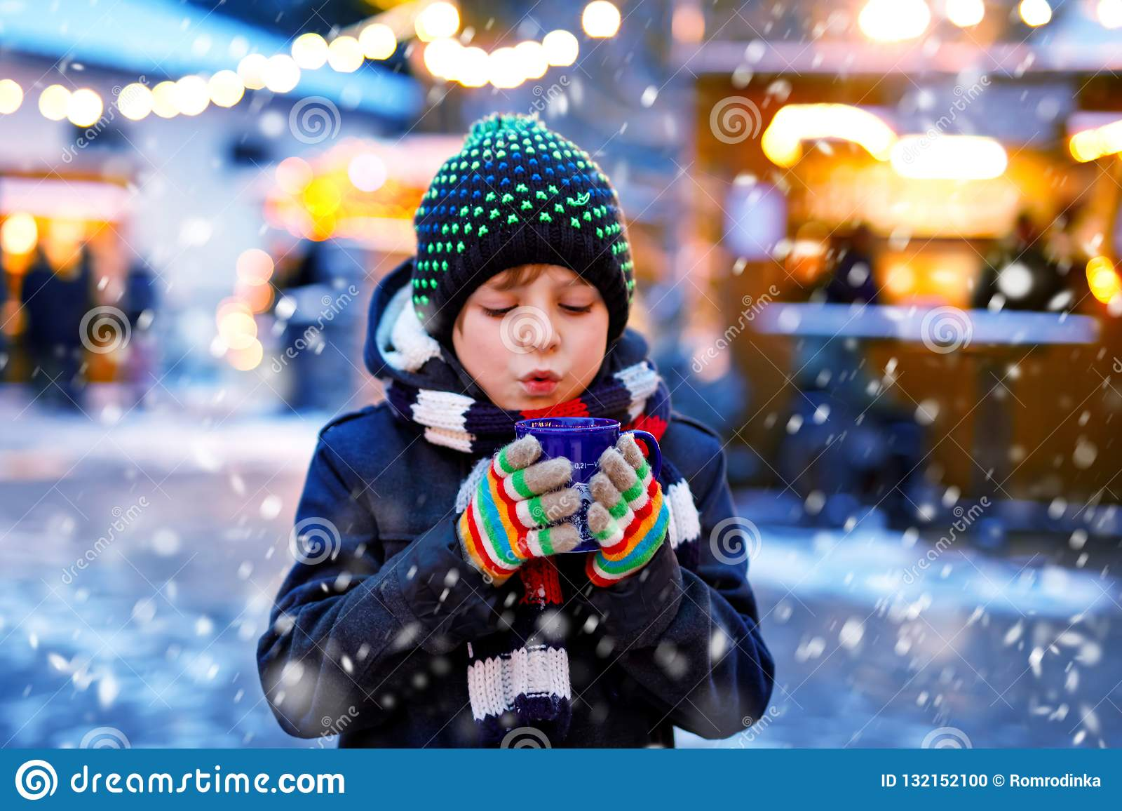 Little cute kid boy drinking hot children punch or chocolate on German Christmas market. Happy child on traditional
