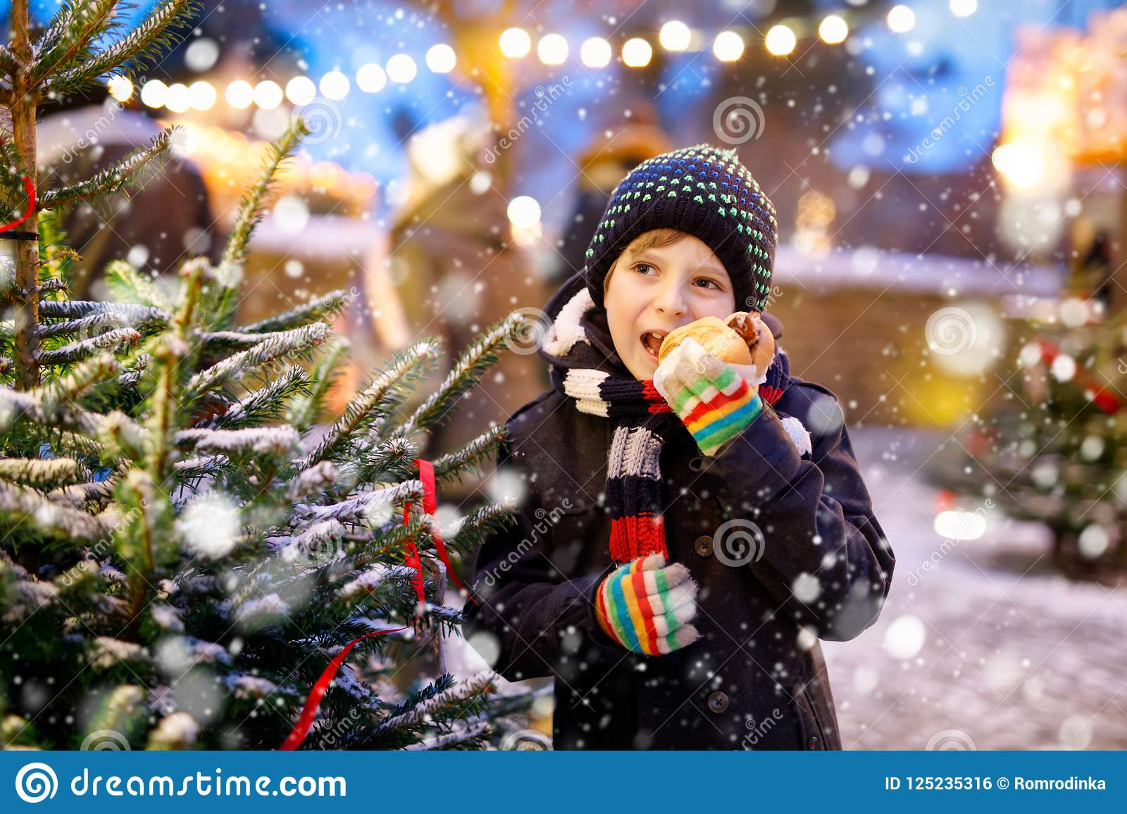 Little cute kid boy eating German sausage and drinking hot children punch on Christmas market. Happy child on
