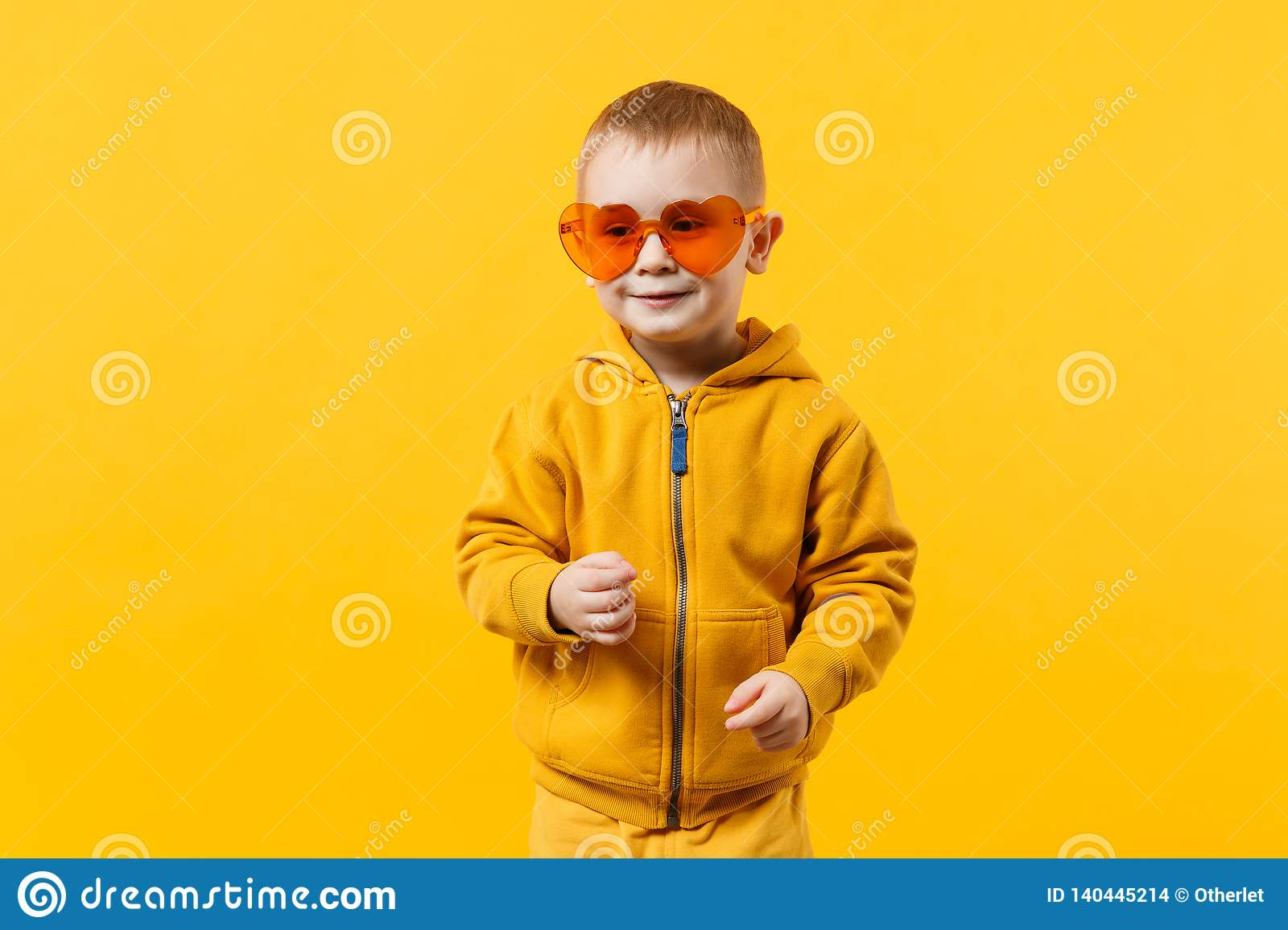 edde9fd67d25 Little cute kid boy 3-4 years old wearing yellow clothes isolated on bright  orange
