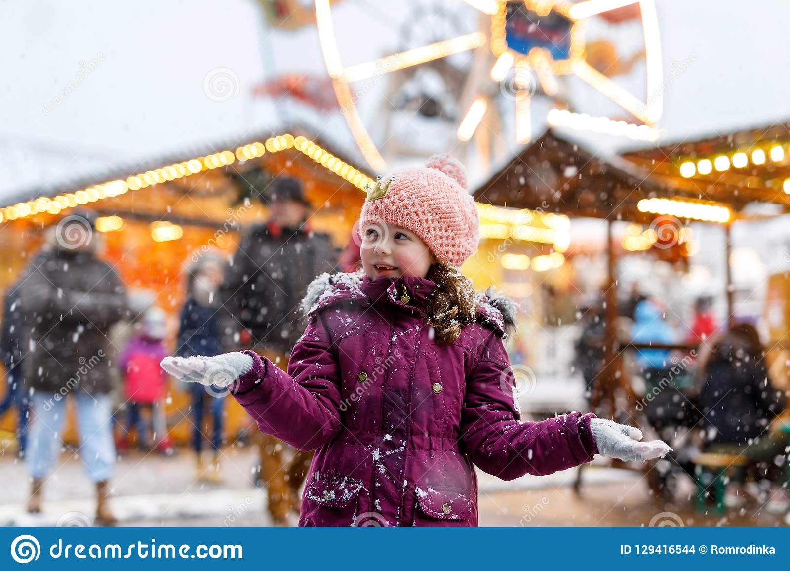 Little cute kid girl having fun on traditional German Christmas market during strong snowfall.. Happy child enjoying