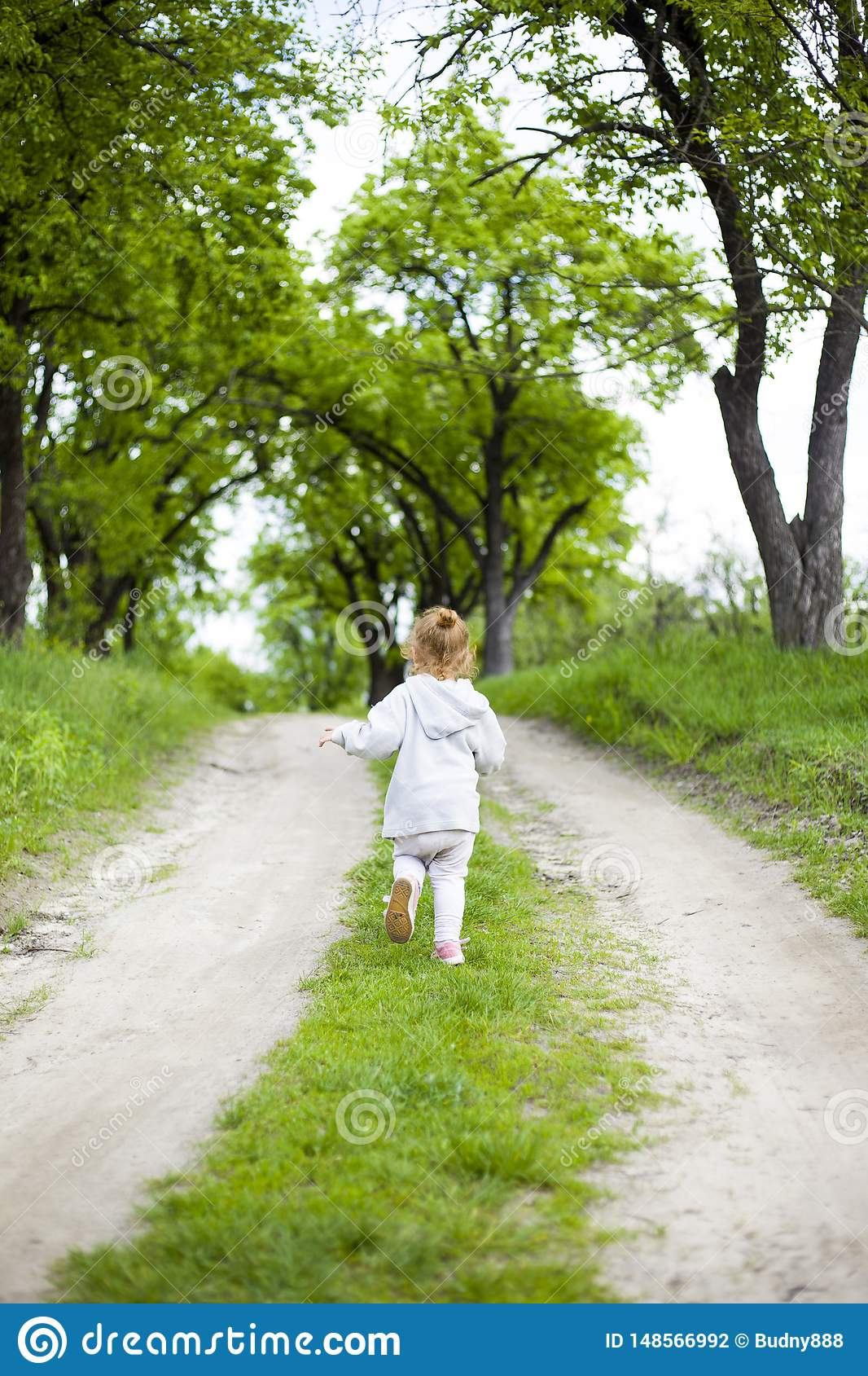 Little cute redhead girl runs along a dirt road with grass and laughs