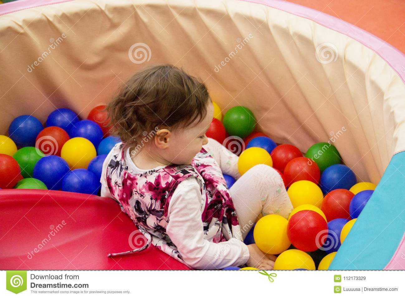 Little cute smile girl plays in balls for a dry pool. Play room. Happiness