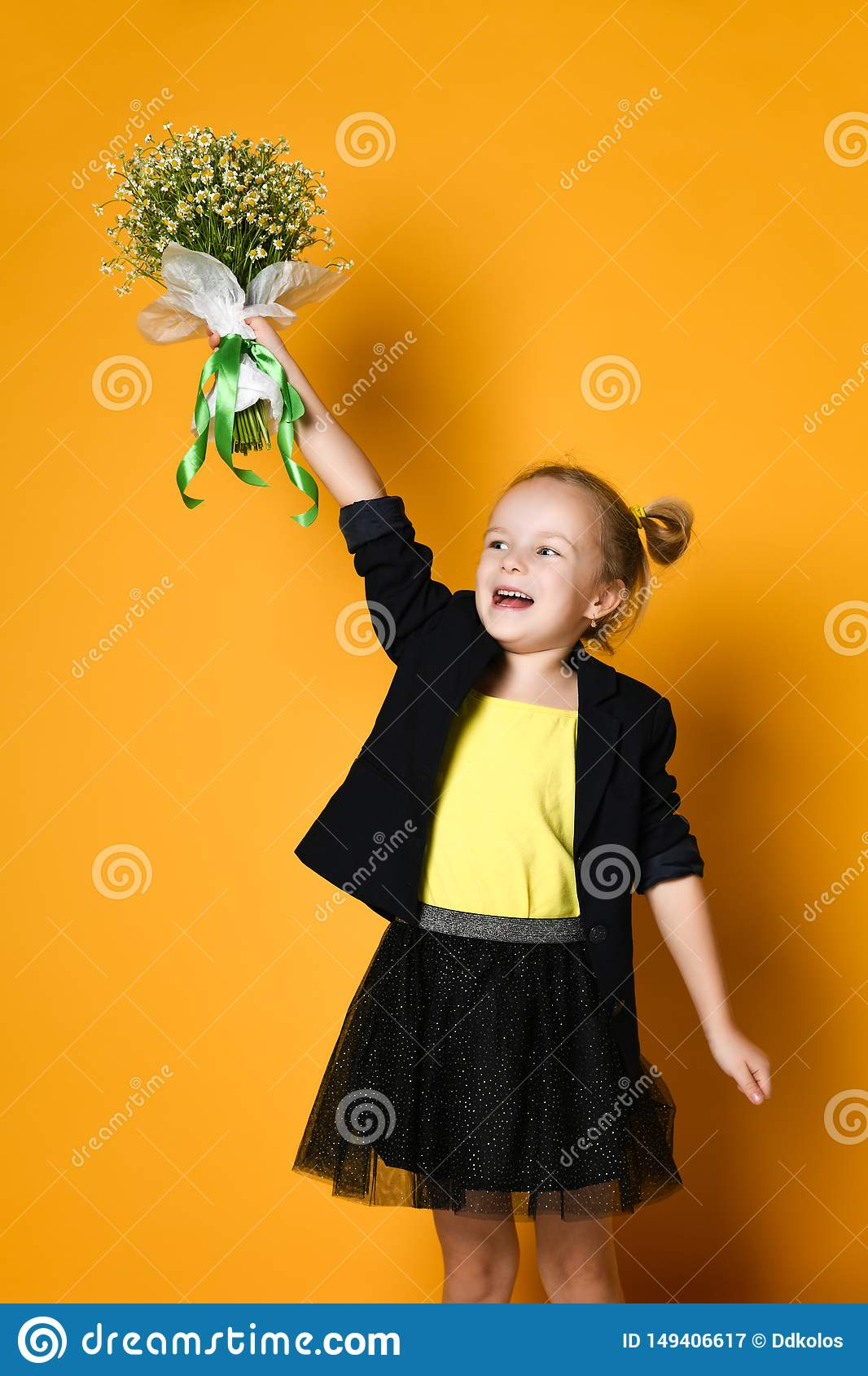 Little cute 5-year-old girl holds a large bouquet of daisies