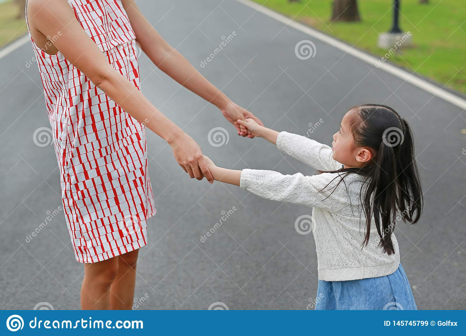 Little daughter holding mother hands in the outdoor nature garden