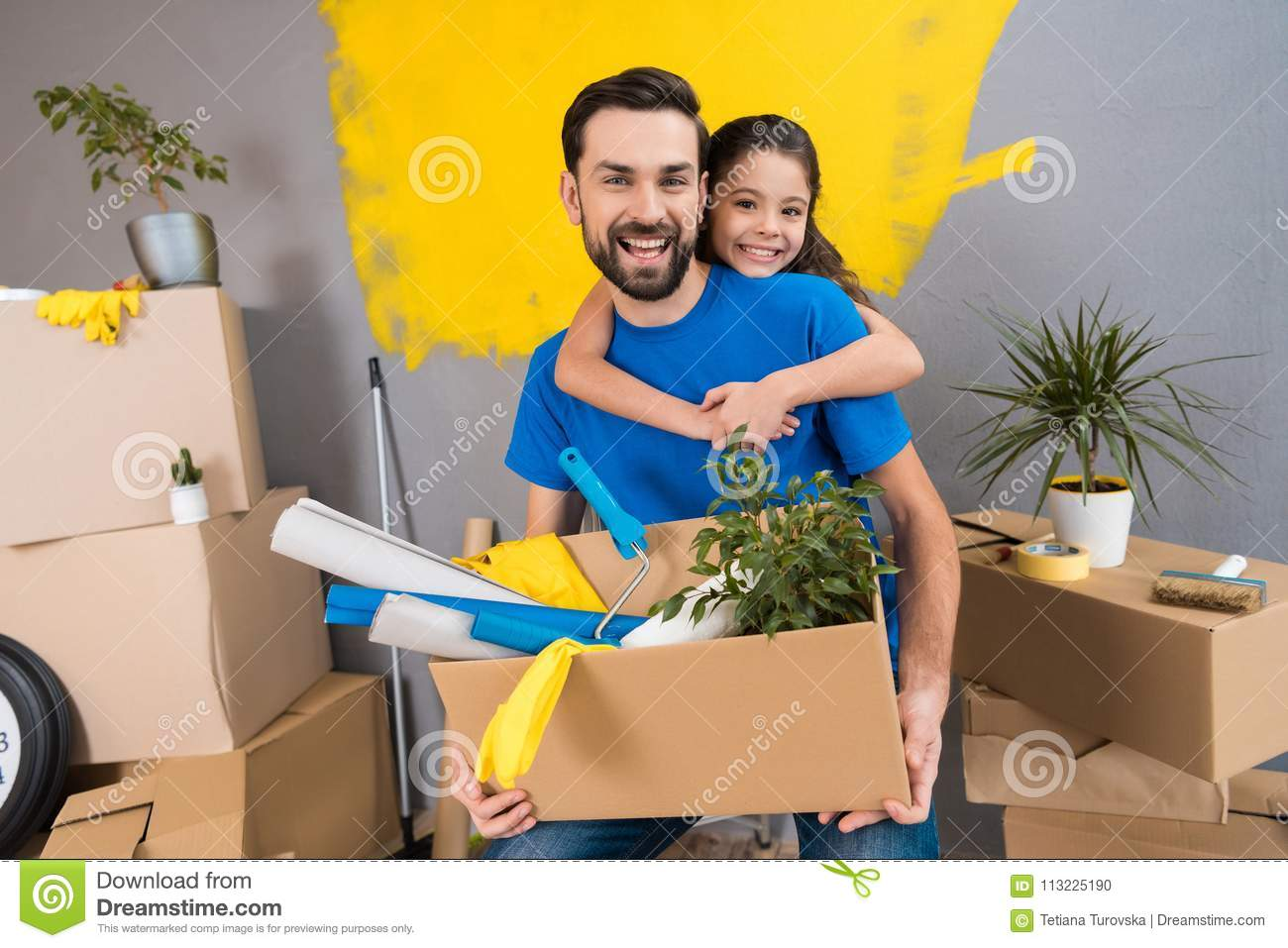 Little daughter hugs her father, who keeps box of tools and things. Family does house repairs together.